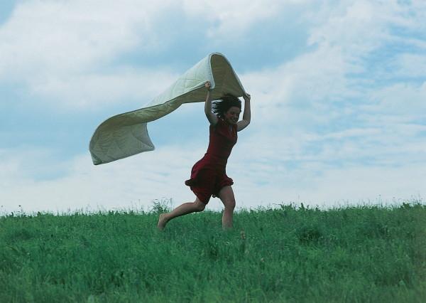 Über eine Wiese laufendes Mädchen mit flatternder Bettware