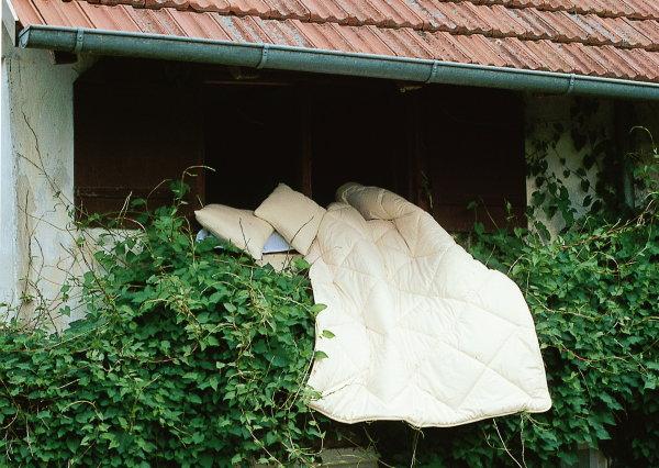 Zum Lüften über Balkongeländer gelegte Bettware aus Wolle